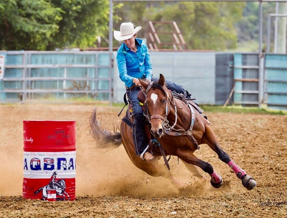 Photo of Kristy banks riding a brown horse. The horse is taking a sharp left turn around a red barrel. Kristy sits on top of the horse in a blue shirt, holding onto the reigns and smiling.
