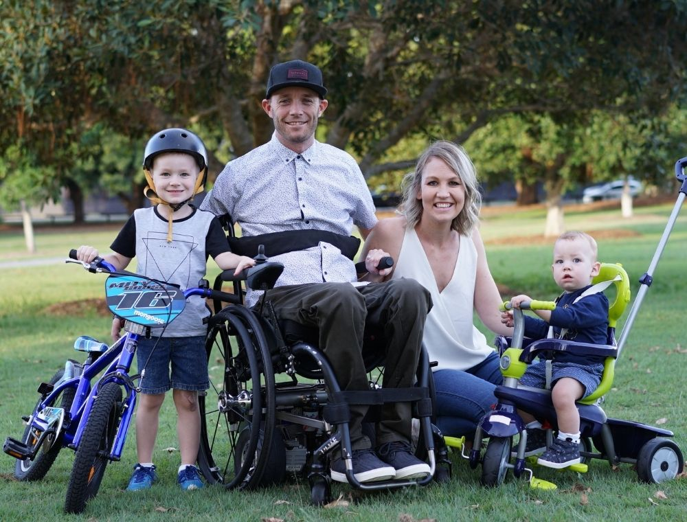 Photo of Dane sitting in his wheelchair at a park surrounded by his family. His wife is on the right of him in a white shirt. His eldest child stands on the left of him, holding a children's bike. On his right, next this himself and his wife, is their youngest child who is sitting on a bright green tricycle.