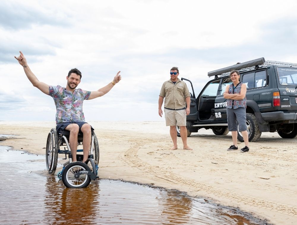 Photo of man in a colourful patterned shirt sitting in a wheelchair on the beach with his hands outstretched. The man's wheelchair is slightly in shallow water. There is a four-wheel-drive behind him with two other people standing in front of the car.