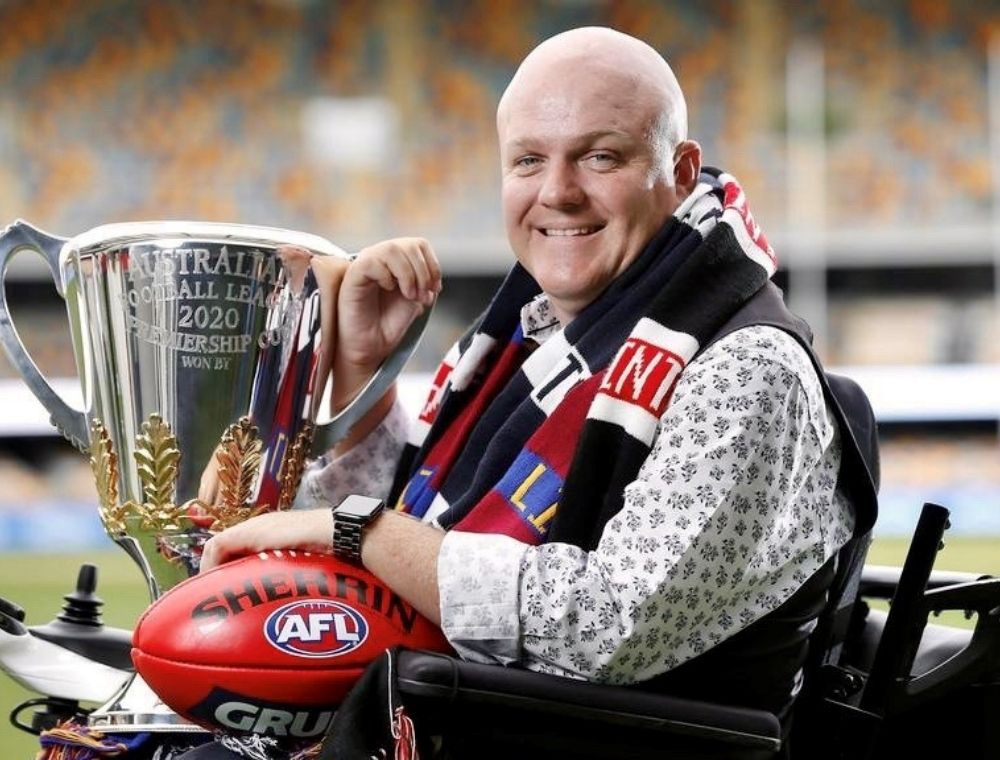 Tim McCallum sitting in his wheelchair smiling at the camera holding the 2020 Premiership Cup and red football.