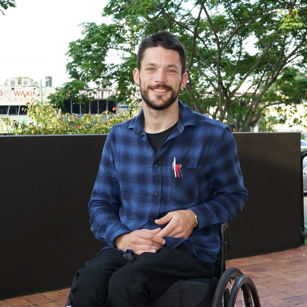 Photo of Lachlan Chapman sitting in a wheelchair smiling at camera
